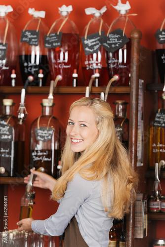lächelnde verkäuferin füllt öl in eine flasche