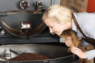 frau schaut auf geröstete kaffeebohnen