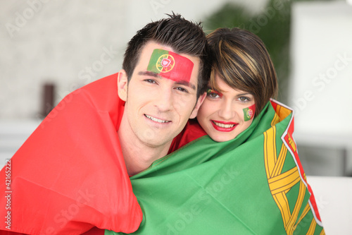 Portuguese soccer fans wrapped in flag