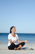 Pretty woman exercising and meditating at beach