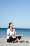 Pretty woman exercising and meditating at beach