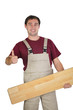 craftsman holding a parquet plank and making a thumbs up sign