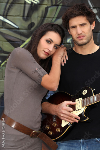 Couple with guitar in front of painted wall