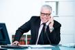 seriöser älterer geschäftsmann am telefon