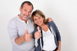 Portrait of senior couple showing thumbs up