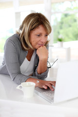 Senior woman in front of laptop with cup of coffee