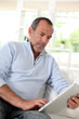 Senior man at home using electronic tablet