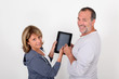 Senior couple having fun with electronic tablet