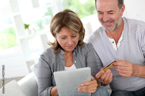 Senior couple using credit card to shop online