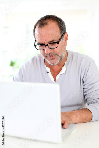 Senior businessman working on laptop from home