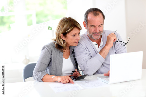 Couple reading construction plan at home with use of laptop
