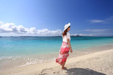 海辺を散歩する後姿の女性