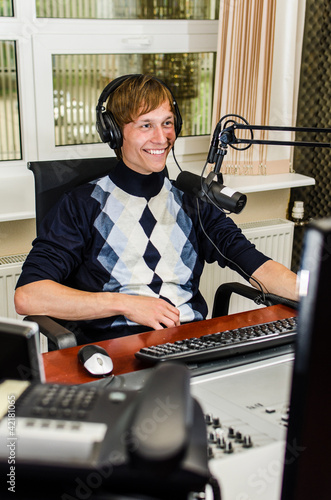 Anchorman sitting in front of a microphone on the radio
