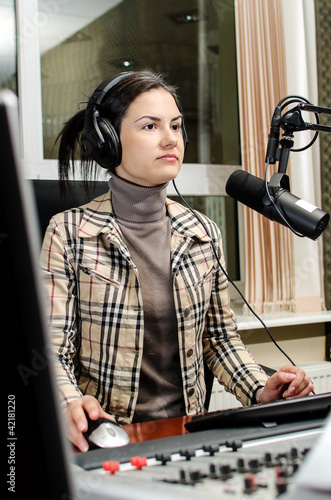 Anchorwoman sitting in front of a microphone on the radio