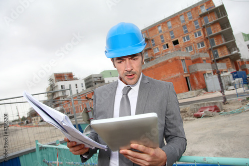 Architect checking plan of construction with tablet