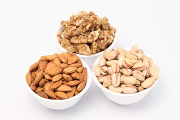 Bowls of almonds,walnuts and pistachios on white background