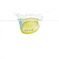 Zitronenscheibe fällt ins Wasser