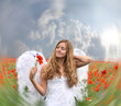 Dreaming angel girl in field of red poppies with white wings