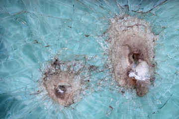 Armour glass with damages from bullets of a machine gun