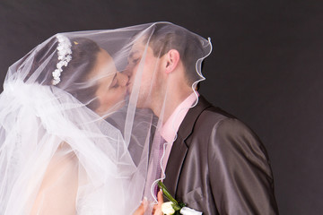 Happy bride and groom kissing under the veil