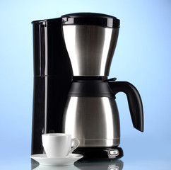 Coffee maker with white cup on blue background