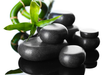 Spa stones and green bamboo on grey background