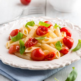 Penne pasta with cherry tomatoes and basil on a plate