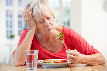 Sick older woman trying to eat