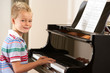 Young boy playing grand piano at home
