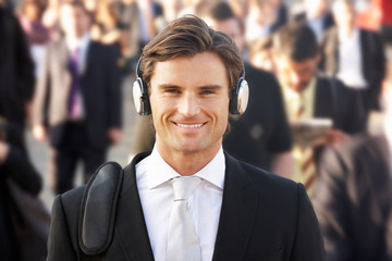 Male commuter in crowd wearing headphones