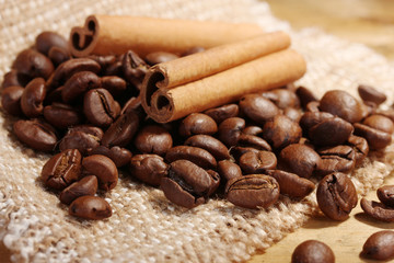 coffee beans and cinnamon sticks on sacking on wooden table