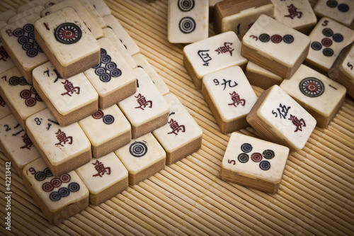 Old chinese game mahjongg on bamboo mat background