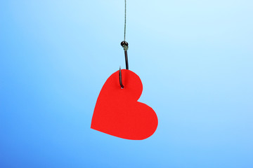 Heart on fish hook on blue background