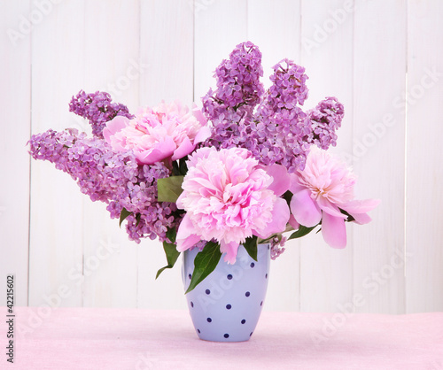 Foto op Canvas Lilac spring flowers in cup on table on white wooden background
