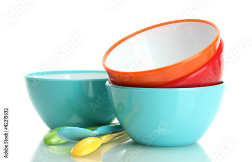 bright empty bowls and spoons isolated on white