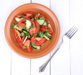 Fresh salad on white wooden background