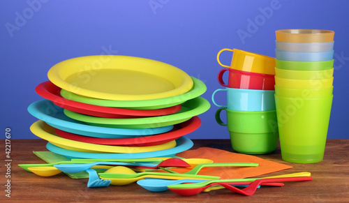 bright plastic tableware on wooden table on colorful background
