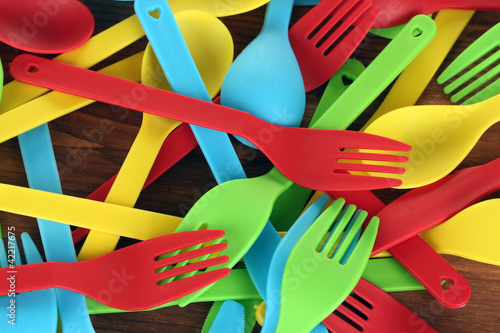 bright plastic tableware on wooden background close-up