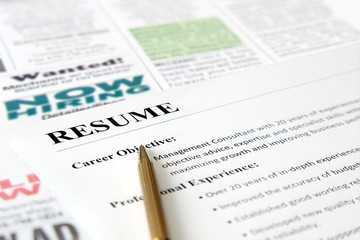 Closeup of resume with pen on the newspaper