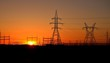 silhouette of high voltage towers in the background of sunset