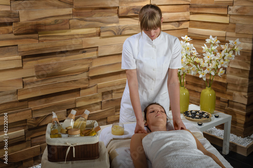 Woman enjoying neck massage at luxury spa