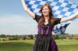 Frau im Dirndl mit bayrischer Flagge