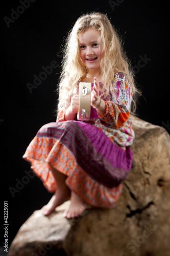Cute girl playing tamburine