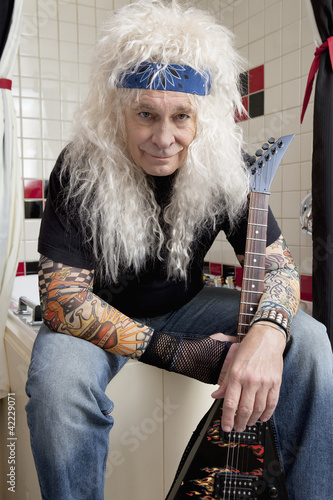 Portrait of guitarist sitting in bathroom