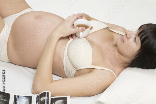 Pregnant woman holding tea cup while lying on bed