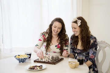Young sisters playing a game of chess