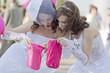 Two girls in a white dress look in pink sacks