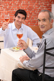 Young man at a restaurant with his grandfather