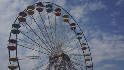 Ferris wheel rotates on cloudy sky background