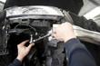 Hands of auto mechanic repairing car